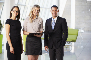 two women and a man in business attire
